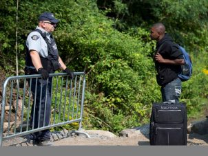 A Haitian man talks with an RCMP officer while waiting to cross the U.S.-Canada border into Quebec last August. (CNS photo - Christinne Muschi, Reuters)