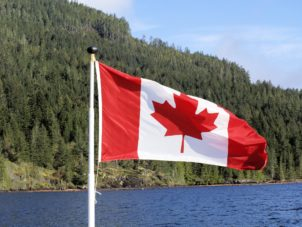 Canadian flag with a lake and woods in the background