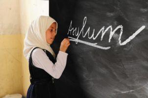 Little refugee girl writing Asylum on the black board